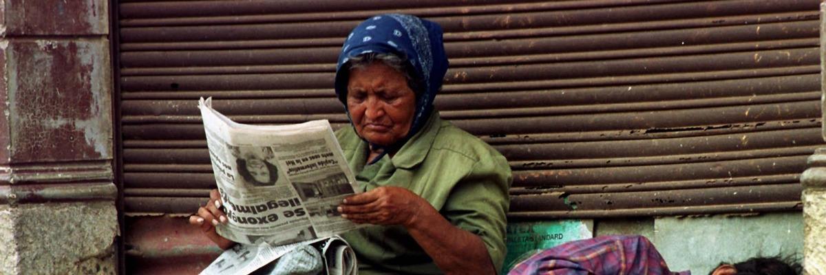 Mulher sem-teto lendo jornal