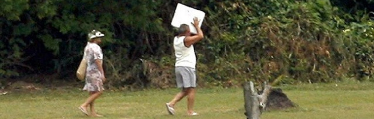 Ex-presidente Lula, seguido pela ex-primeira dama carregando uma caixa de isopor, quando estava de férias.